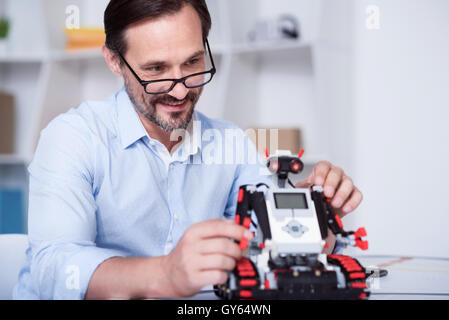 Smart scientist working on a robot production - Stock Photo