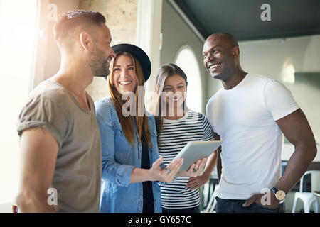 Successful young business team of enthusiastic modern young people in informal clothing standing in the office having - Stock Photo