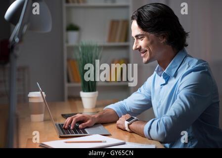 Good looking man working on laptop. - Stock Photo
