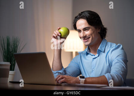 Good looking young man working on laptop. - Stock Photo