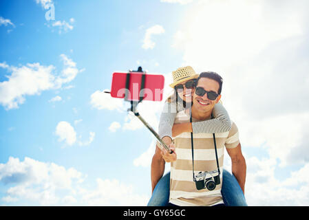 Happy young couple on summer vacation having fun taking a selfie on a stick with the young woman riding piggy back - Stock Photo