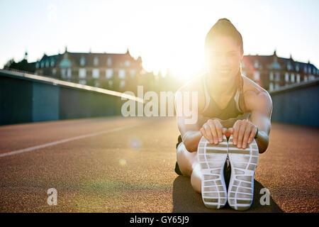 Athlete limbering up before her workout sitting on a tarred bridge doing stretching exercises backlit by a bright - Stock Photo