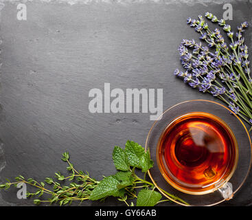Herbal tea in a glass cup, different types of herbs: lavender, mint, thyme on black stone background (top view) - Stock Photo