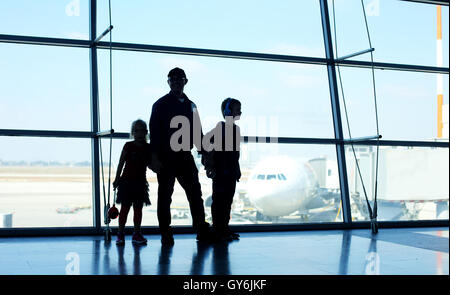Silhouette of father and two kids standing in front of the window in airport - Stock Photo