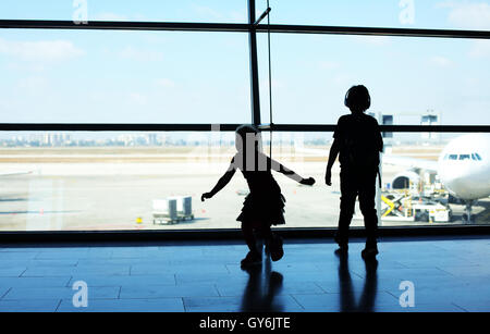 Silhouette of two kids standing in front of the window in airport - Stock Photo