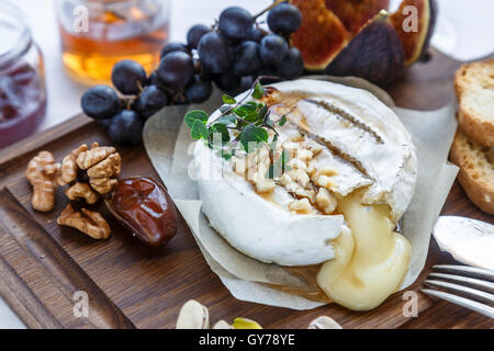 Baked camembert cheese with figs, honey, grapes and nuts. Top view - Stock Photo
