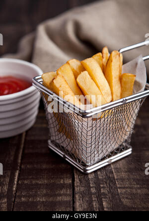 Fried french fries chips in fryer with ketchup on wood - Stock Photo