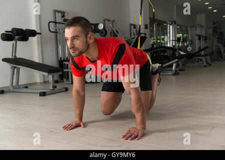 Fitness Instructor Exercising Crossfit With Trx Fitness Straps In The Gym's Studio - Stock Photo