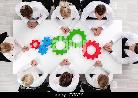 Business team sitting around the table with cogs, teamwork concept - Stock Photo