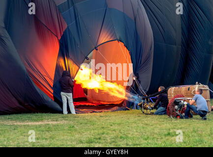 hot air balloon pilots inflating hot air balloon with the burner and the fan - Stock Photo