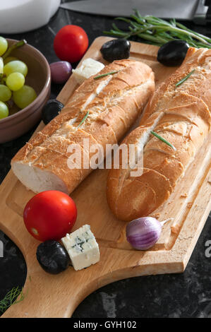 Two bread baguettes and ingredients on wooden cutting board - Stock Photo