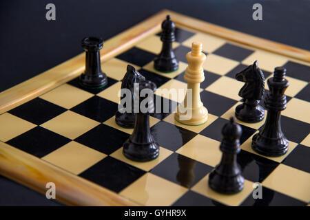 Black chess pieces surrounding white king. Close view. - Stock Photo