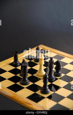 White chess pieces surrounding black king. Close view. - Stock Photo