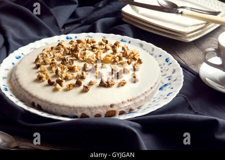 Homemade pumpkin and walnut cake with cream icing over rustic wooden table - healthy homemade pastry - Stock Photo
