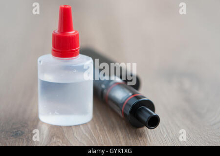 Vaping device vaporizer and container with e-liquid or e-juice. Refill liquid tobacco with propylen glicol and glycerin - Stock Photo