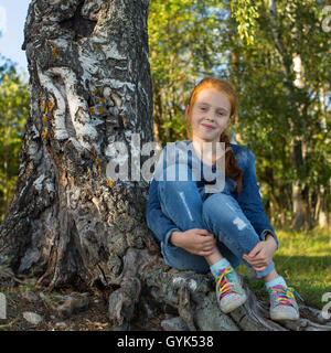 Little girl sitting in the woods near birch. - Stock Photo