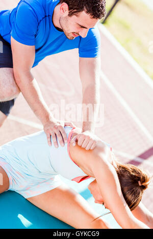 Trainer helping during strech out, outdoors shot - Stock Photo