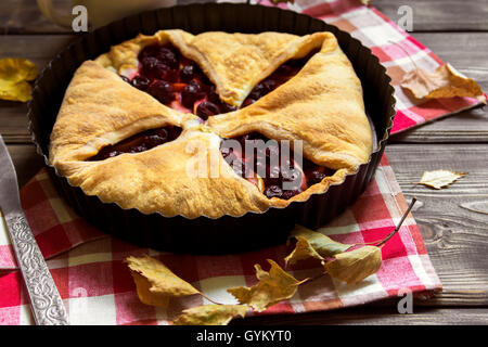 Homemade cherry and apple pie over rustic wooden background with yellow leaves, copy space - delicious autumn pastry - Stock Photo