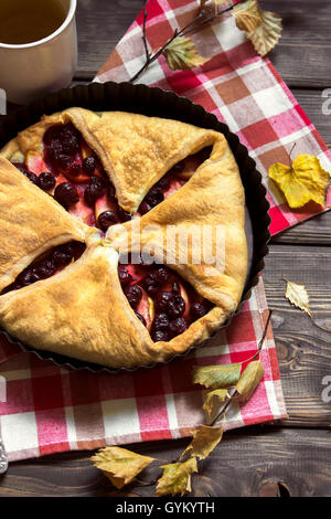 Homemade cherry and apple pie over rustic wooden background with yellow leaves - delicious autumn pastry - Stock Photo
