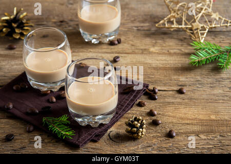 Irish cream coffee liqueur with Christmas decoration and ornaments over rustic wooden background - festive Christmas - Stock Photo