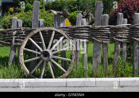 Rustic wheel of a traditional cart leaning on a wooden fence - Stock Photo