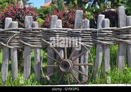 Old wheel of a traditional cart leaning on a wooden fence - Stock Photo