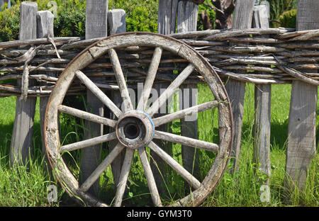 Closeup of an old wheel of a traditional cart leaning on a wooden fence - Stock Photo