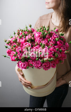 Luxury bouquets of flowers in the hat box. roses in the hands women. Pink Colour peonies