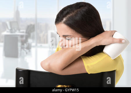 Businesswoman sitting in a chair tired and sleepy, isolated in white - Stock Photo
