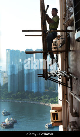 A construction worker on a very high scaffolding in Hong Kong. - Stock Photo
