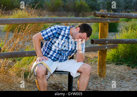 Alone time outdoors man praying with his head in his hand and Bible in his lap. - Stock Photo