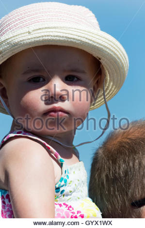 Little girl, in a hat and sun dress, sitting on her fathers shoulders in the summer sunshine - Stock Photo