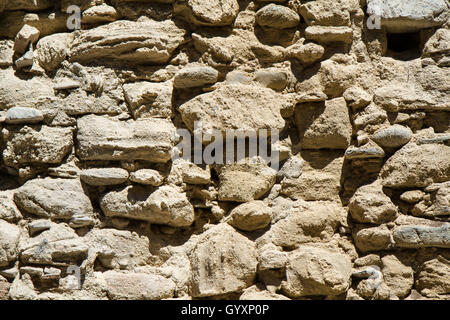 detail of the old wall of the ruined stones and without plaster