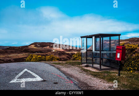 Shelter for hikers and red post box on the street, Highland, Scotland, United Kingdom - Stock Photo