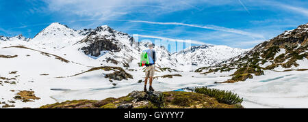 Hiker stands in front of mountain landscape, snow melts, Rohrmoos-Untertal, Schladming Tauern, Schladming, Styria, - Stock Photo