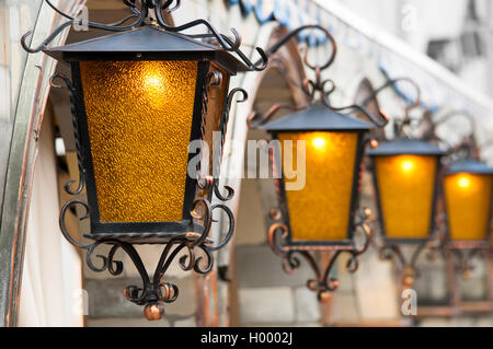 Four brass lanterns hanging on arc facade - Stock Photo