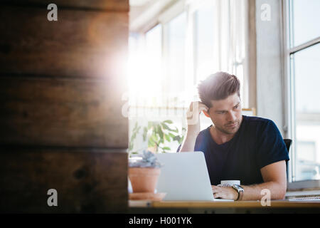 Young business man with problems and stress in the office. Man at his desk with laptop and looking away thinking. - Stock Photo