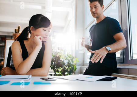 Two young executives discussing new business ideas in office. Colleagues working together on paperwork. - Stock Photo
