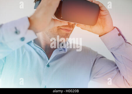 Closeup shot of businessman wearing virtual reality goggles against grey background. Young man using VR glasses - Stock Photo