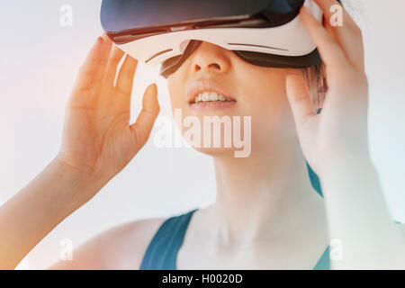 Close up shot of asian woman using the virtual reality headset and looking away. Female wearing VR goggles against - Stock Photo