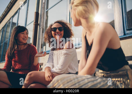 Three young women meeting at outdoor cafe chatting and enjoying. Group of female friends having fun while sitting - Stock Photo