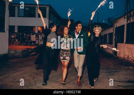 Full length shot of four young friends walking down the city street with fireworks and celebrating new years eve. - Stock Photo