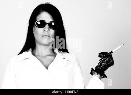 elegante Frau mit Sonnenbrille und Zigarette, Deutschland | woman wearing sunglasses, Germany | BLWS100664.jpg [ - Stock Photo