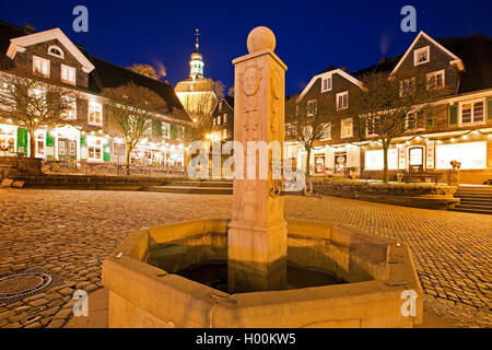 historic fountain on market place and monastery church in the old city of Graefrath in the evening, Germany, North - Stock Photo