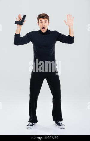 Full length of scared young man holding gun and standing with hands up - Stock Photo