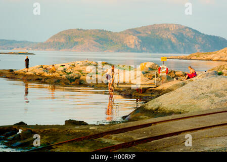 Marstrand, Sweden - September 8, 2016: Documentary of male climbing down a ladder to take a short evening swim in - Stock Photo