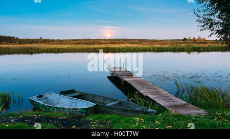 Wooden Boards Pier On Calm Water Of Lake, River And Two Rowing Fishing Boats. Moon Rise Over Evening Water. - Stock Photo