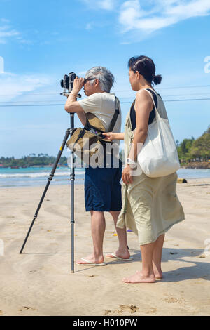 WELIGAMA, SRI LANKA - MARCH 7, 2014: Japanese tourists stand on sandy beach and take photos with old film camera. - Stock Photo
