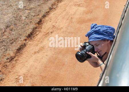 YALA NATIONAL PARK, SRI LANKA - MARCH 4, 2014: Female tourist taking photos during safari jeep tour in the Yala - Stock Photo