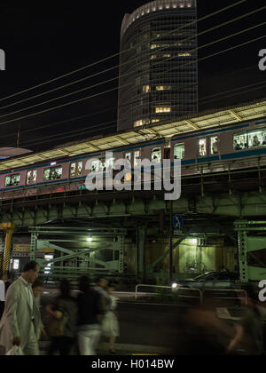 Pedestrians walk on busy night street below Yamanote Line passenger train at Yurakucho Station, Tokyo, Japan - Stock Photo